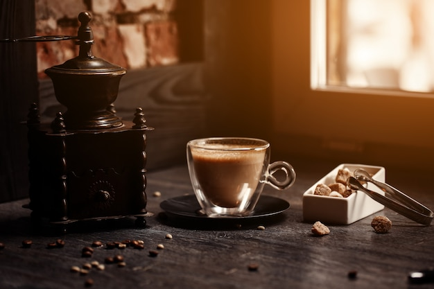Cup of coffee in coffee. grinder and cane sugar on table with flare blurred background.
