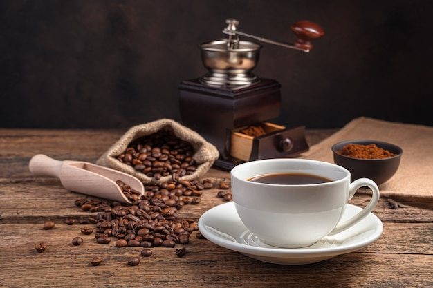 A cup of coffee, a coffee grinder, and grains on a brown wall with space to copy. side view.