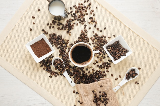 Cup of coffee; coffee powder; coffee beans and small sack on placemat