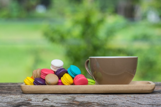 Cup of coffee and colorful macaroons in dish on wooden table