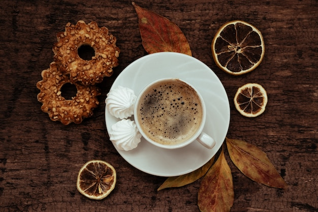 Cup of coffee, cookies and autumn leaves on wooden table, top view.