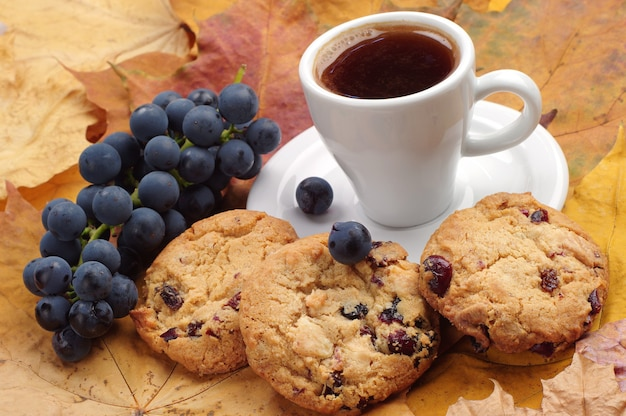 Cup of coffee, cookies and grape on autumn leaves