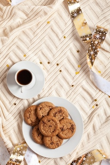 Cup of coffee and cookies on a knitted blanket