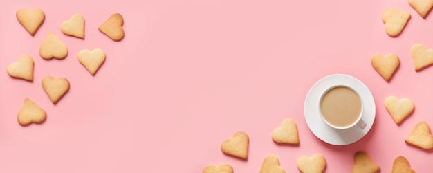 Cup of coffee and cookies shaped of heart on pink. valentine card. flat lay, copy space.