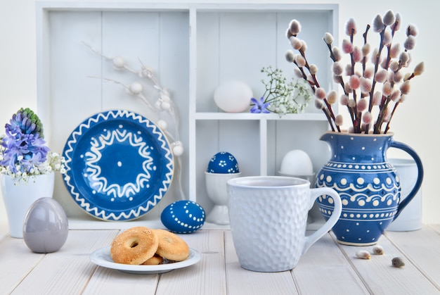 Cup of coffee and cookies on white table with bunch of pussy-willow in blue ceramic jar