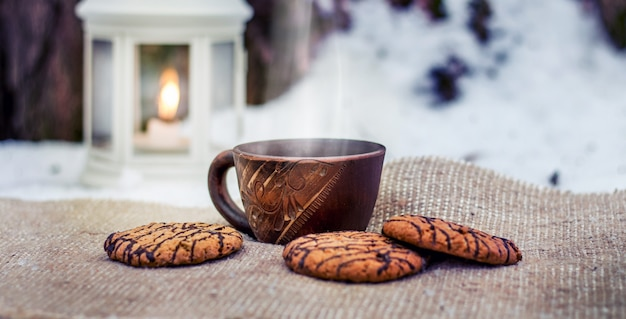 Cup of coffee and cookies in winter forest in the evening near lantern with candle