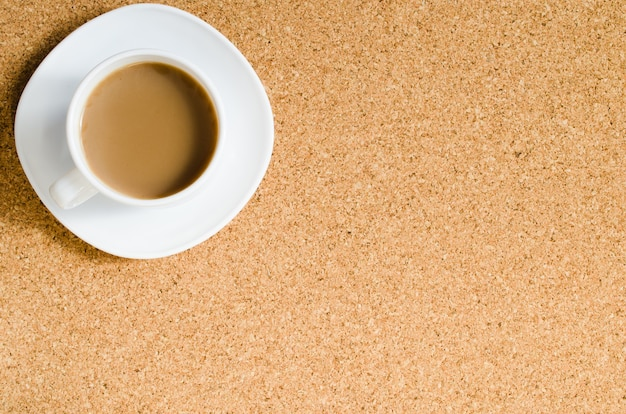 Cup of coffee on cork board.