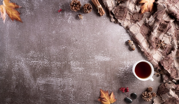 A cup of coffee cotton flowers autumn leaves and scarft on dark stone background