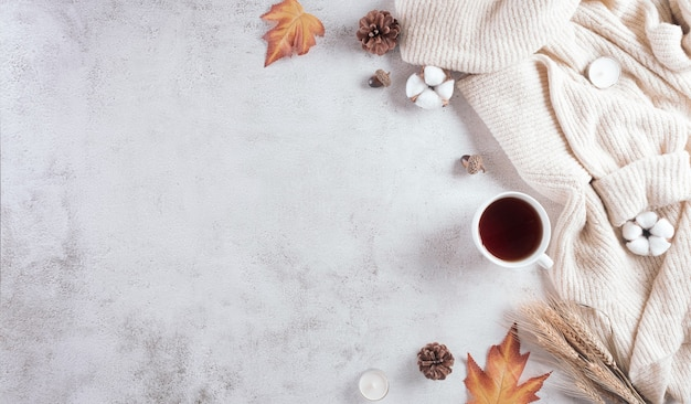 A cup of coffee cotton flowers autumn leaves and sweater on stone background