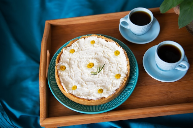 A cup of coffee and cream cheesecake stand on a wooden tray in bed.