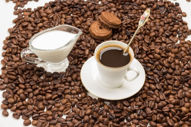 Cup of coffee, cream and cookies among roasted coffee beans. top view