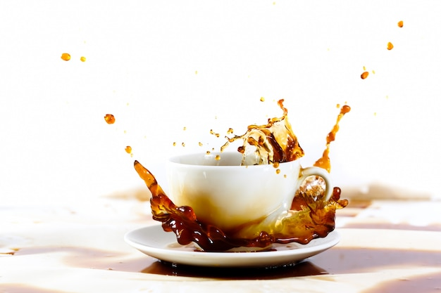 Cup of coffee creating splash