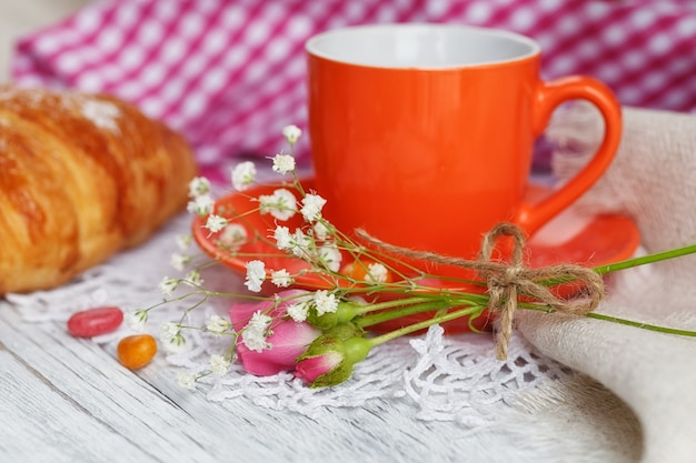 Cup of coffee and croissant are decorated by napkins, roses and candies on a white wooden table.