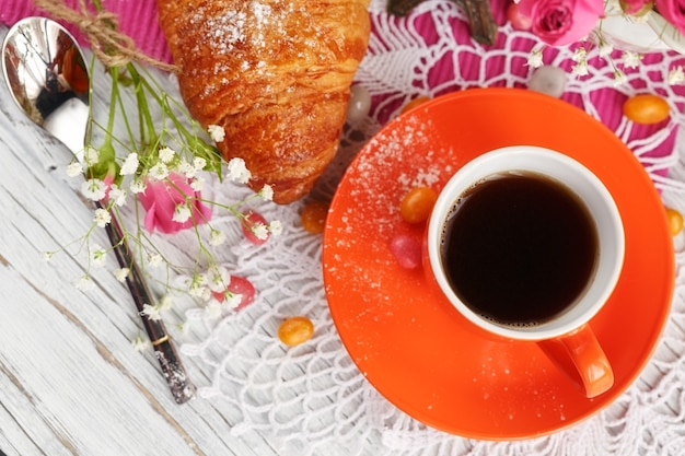 Cup of coffee and croissant are decorated by the small eiffel tower, napkins, roses and candies on a white wooden table
