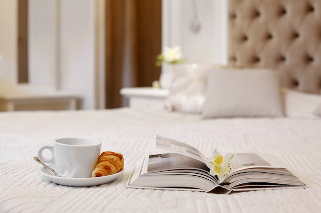 Cup of coffee, croissant and a book on the bed in a bright comfortable room