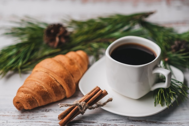 Cup of coffee and a croissant for christmas breakfast, decorated with fir branches and pine cones