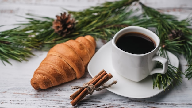 Cup of coffee and a croissant in new year decor. christmas winter holiday breakfast