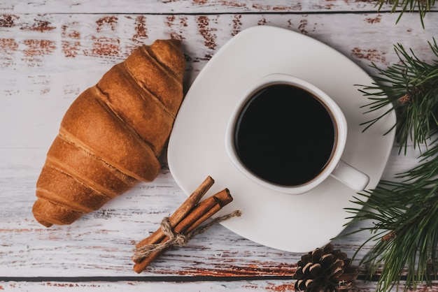 Cup of coffee and a croissant in new year decor, christmas winter holiday breakfast