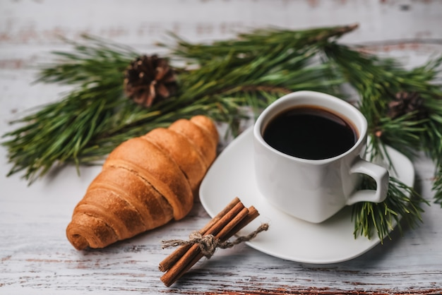 Cup of coffee and a croissant in new year decor.
