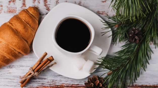 Cup of coffee and a croissant in new year decor