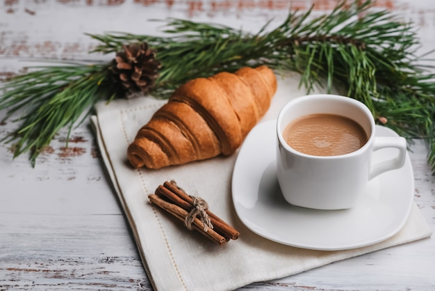 Cup of coffee and a croissant on table. the concept of a christmas greeting card