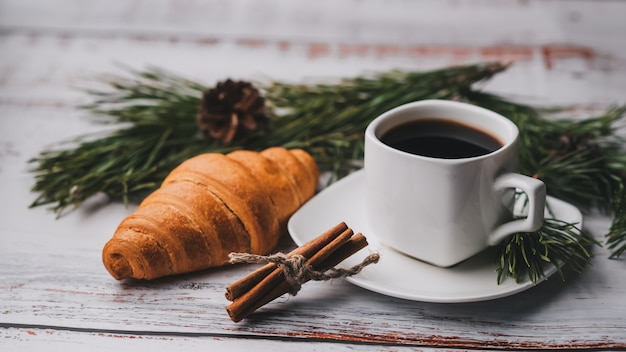Cup of coffee and a croissant on table