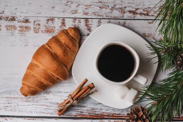 Cup of coffee and a croissant on table.