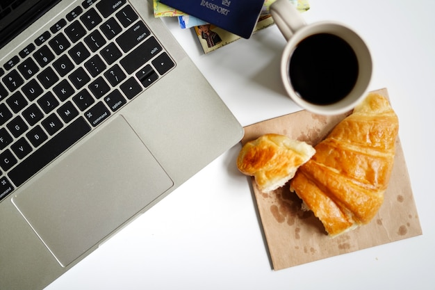 Cup of coffee and croissant with planning vacation trip and ready to go