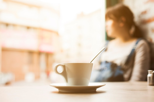 Cup of coffee cup in front of defocus woman looking away