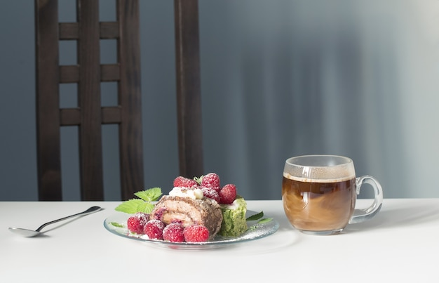 Cup of coffee and dessert with raspberries on white table on background blue wall