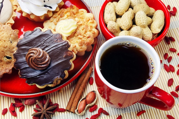 Cup of coffee, different cakes and peanuts closeup