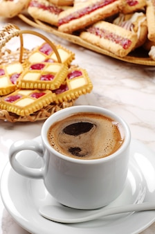 Cup of coffee and different cookies on table