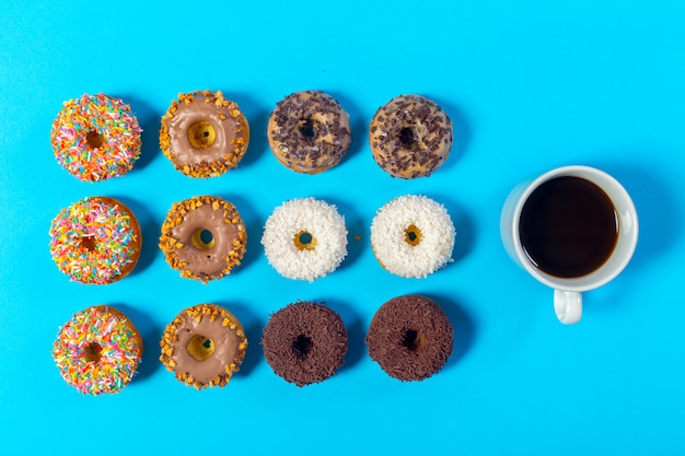 Cup of coffee and donut isolated on blue background