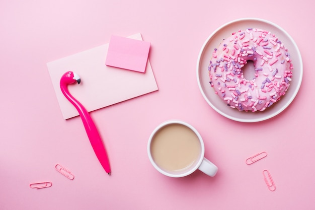 Cup of coffee, donut pen flamingo notepad on pink. concept office. flat lay.