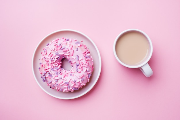 Cup of coffee and a doughnut on pink. top view flat lay.