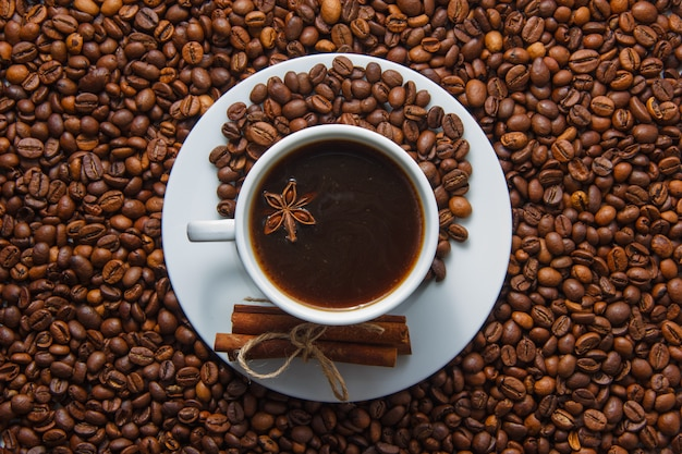 A cup of coffee and dry cinnamon with coffee beans on background. top view.
