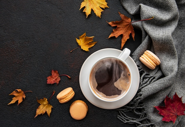 Cup of coffee and dry leaves on black concrete background. flat lay, top view, copy space