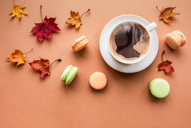 Cup of coffee and dry leaves on brown background. flat lay, top view, copy space