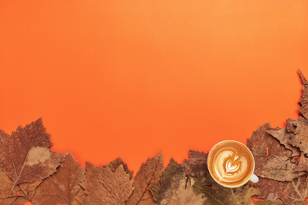 Cup coffee and dry leaves on orange background