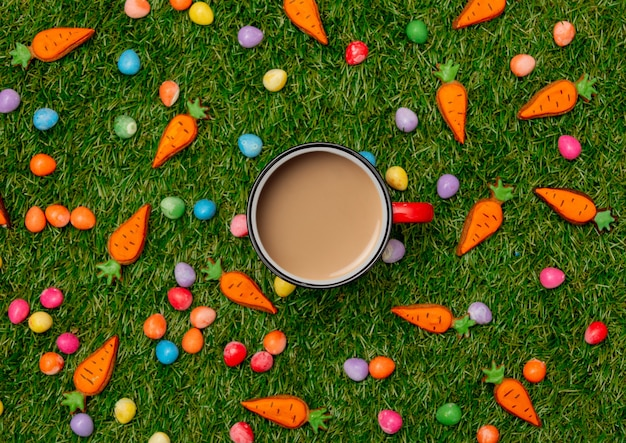 Cup of coffee and easter chocolate eggs with cookie carrots on green grass
