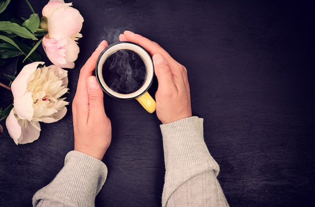 Cup of coffee in female hand on black
