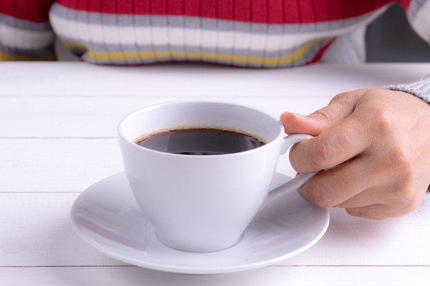 Cup of coffee in female hand on white wooden table.