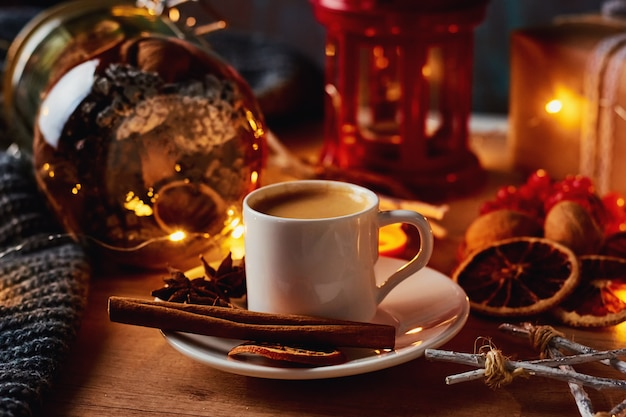 Cup of coffee in festive decorations with a fairy garland lights