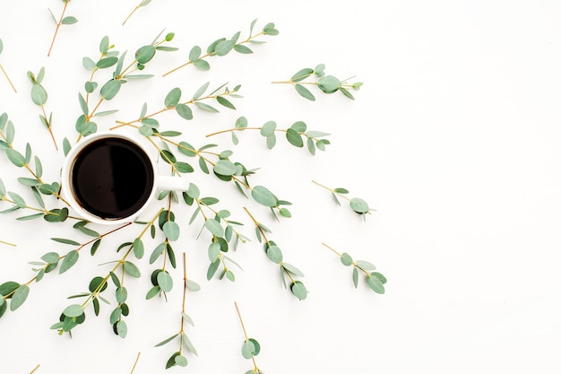 Cup of coffee in frame of eucalyptus branch. flat lay, top view
