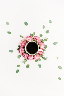 Cup of coffee in frame of pink rose flower buds and eucalyptus branches on white