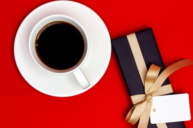 Cup of coffee and gift box with blank white tag on red background.