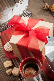 Cup of coffee, gift with red ribbon, brown sugar