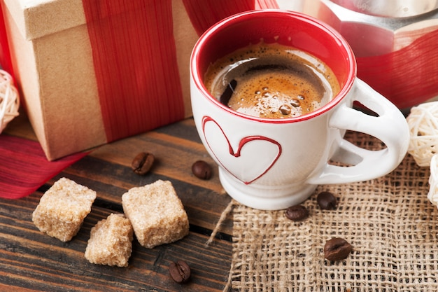 Cup of coffee and gift with red ribbon