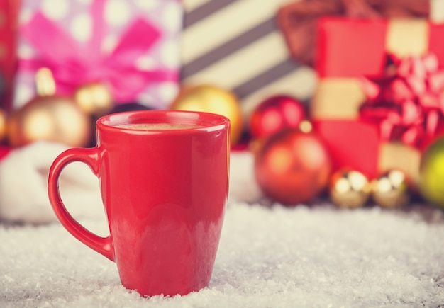 Cup of coffee and gifts at background