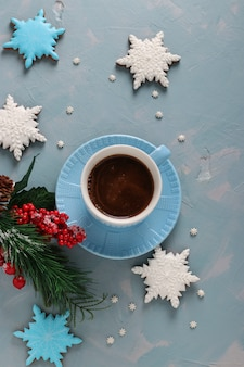 Cup of coffee and gingerbread cookies in the shape of snowflakes on a light blue